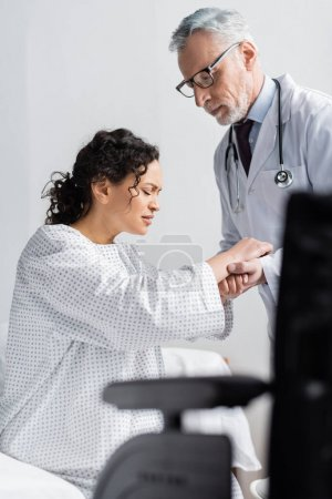 attentive doctor supporting african american woman frowning from pain near wheelchair on blurred foreground