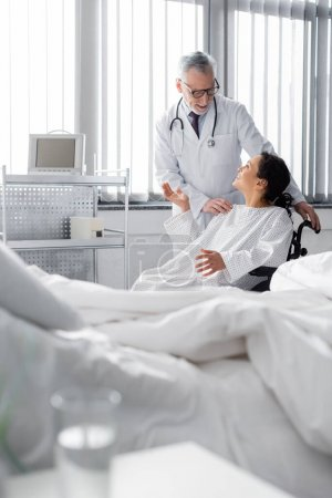 happy african american woman in wheelchair gesturing while talking to doctor near bed on blurred foreground