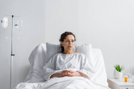 Photo for Ill african american woman with nasal cannula sitting in hospital bed and looking away - Royalty Free Image