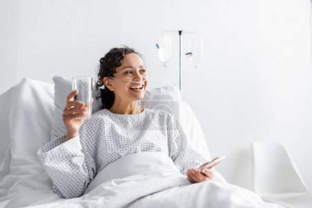 Photo for Happy african american woman smiling while holding glass of water and mobile phone in clinic - Royalty Free Image
