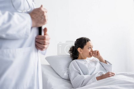 Photo for Upset african american woman looking away near doctor on blurred foreground in hospital - Royalty Free Image