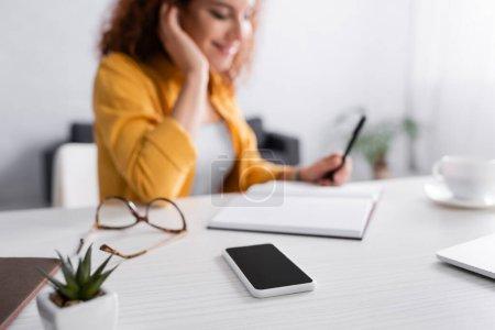 Photo pour Foyer sélectif du smartphone avec écran vide près freelance sur fond flou - image libre de droit