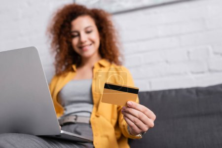 selective focus of credit card in hand of woman with laptop on blurred background