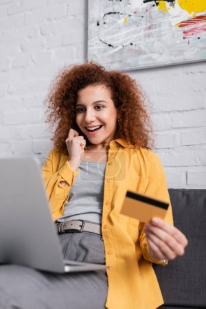 Photo for Happy woman holding credit card near laptop on blurred foreground - Royalty Free Image