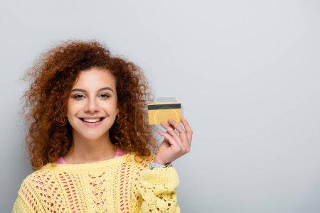 Photo pour Joyeuse femme en pull ajouré tenant la carte de crédit isolée sur gris - image libre de droit
