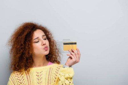Photo pour Femme bouclée soufflant l'air baiser tout en tenant la carte de crédit isolée sur gris - image libre de droit