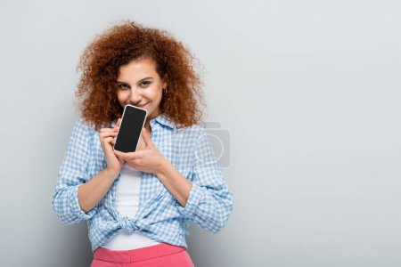 cheerful woman looking at camera while holding cellphone with blank screen on grey background