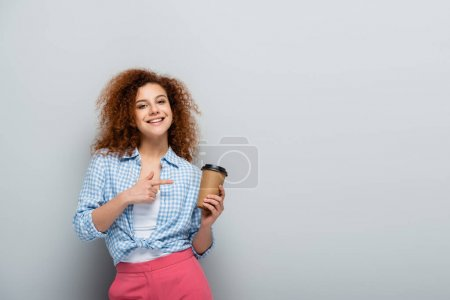 Photo for Pleased woman pointing at paper cup while looking at camera on grey background - Royalty Free Image