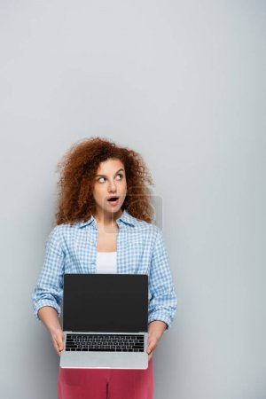 surprised woman with open mouth holding laptop with blank screen on grey background