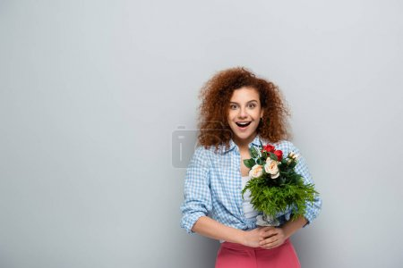 amazed woman looking at camera while holding flowers on grey background