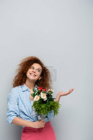 cheerful woman looking up and pointing with hand while holding flowers on grey background