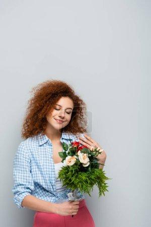 mujer complacida con el pelo rizado sosteniendo flores sobre fondo gris