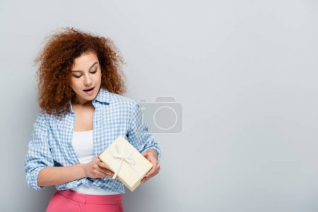 amazed woman in checkered shirt holding present on grey background