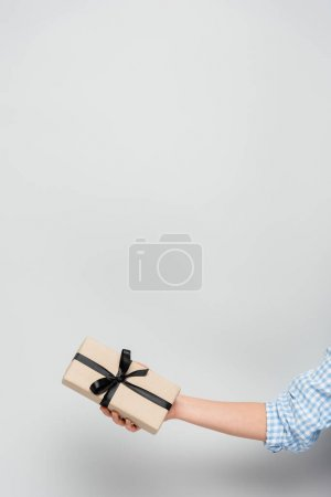 cropped view of woman holding gift box with black ribbon on grey background with copy space