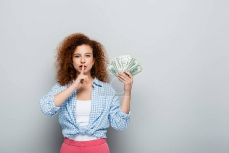 curly woman showing hush gesture while holding dollars on grey background