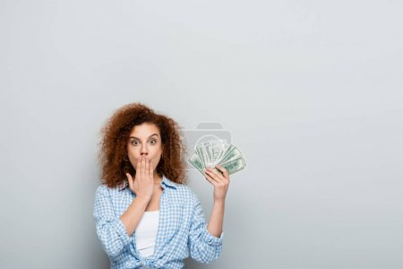 amazed woman covering mouth with hand while holding money on grey background