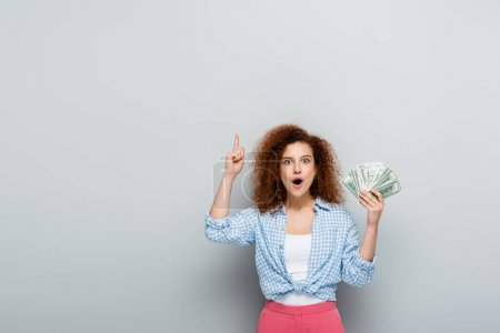 excited woman pointing up with finger while holding dollars on grey background