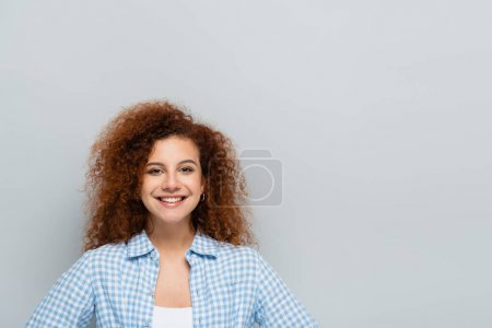 curly woman in plaid shirt smiling at camera isolated on grey
