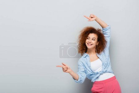 cheerful woman looking away and pointing with fingers on grey background