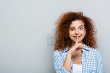 Photo pour Femme joyeuse regardant la caméra tout en montrant le signe shh isolé sur gris - image libre de droit