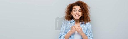 Photo pour Femme excitée montrant geste d'espoir avec poings serrés isolés sur gris, bannière - image libre de droit