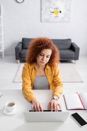 Photo for Freelancer with wavy hair typing on laptop near smartphone with blank screen and coffee cup - Royalty Free Image