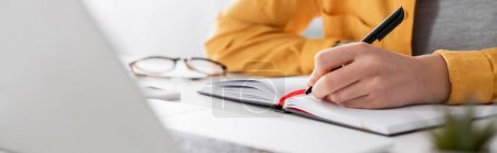 Photo for Partial view of freelancer writing in notebook on blurred foreground, banner - Royalty Free Image