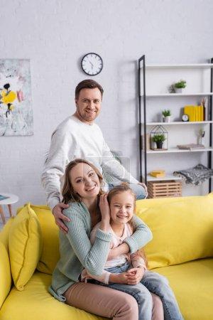 Fröhlicher Mann blickt in Kamera in der Nähe seiner Frau und umarmt Tochter