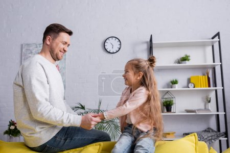 Photo for Man holding hand of smiling daughter at home - Royalty Free Image