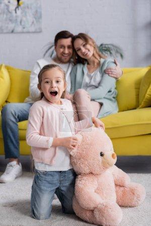 Enfant étonnant tenant ours en peluche près des parents sur le canapé sur fond flou