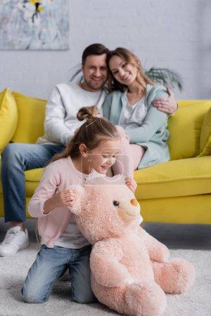 Enfant regardant ours en peluche près des parents flous dans le salon