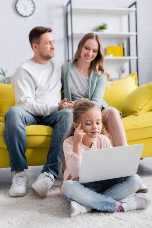 Fille en utilisant un ordinateur portable pendant l'éducation en ligne près des parents sur fond flou