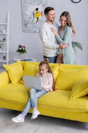 Photo pour Enfant incroyable utilisant un ordinateur portable près de parents joyeux étreignant à la maison - image libre de droit