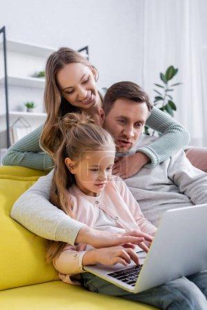 Femme étreignant mari en utilisant un ordinateur portable près de l'enfant à la maison