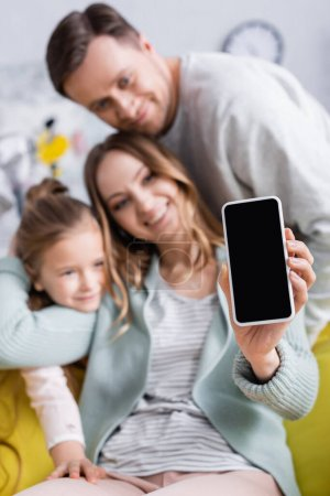 Photo for Cellphone with blank screen in hand of woman near family on blurred background at home - Royalty Free Image