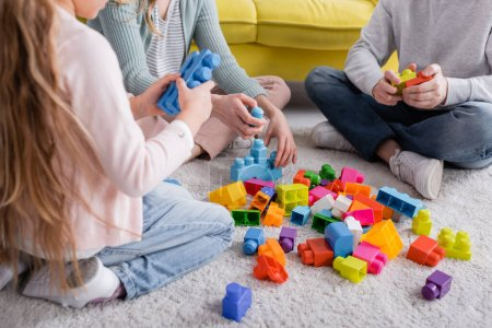 Cropped view of family near colorful building blocks on floor