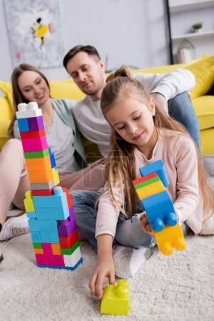 Photo for Kid stacking building blocks near parents in living room - Royalty Free Image