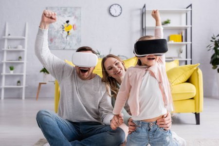 Excited girl and father using virtual reality headsets near mother at home