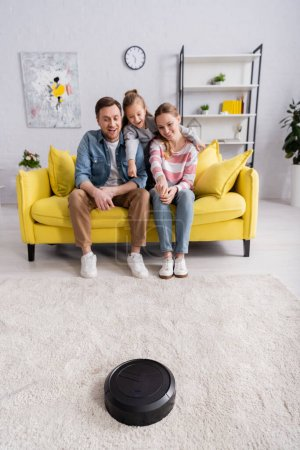 Smiling woman pointing at robotic vacuum cleaner near family