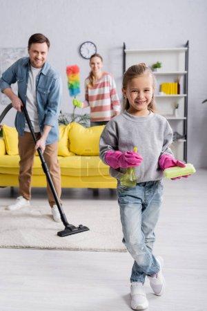 Enfant souriant tout en tenant détergent et chiffon près des parents avec des fournitures de nettoyage