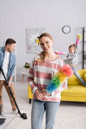 Smiling woman holding dust brush near family on blurred background