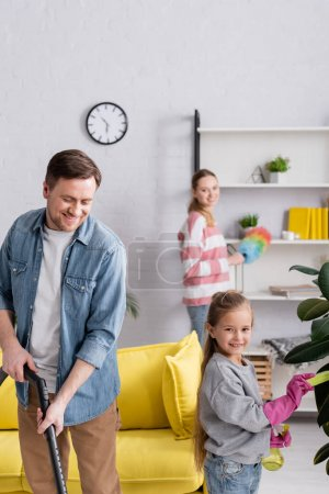 Smiling father holding vacuum cleaner near daughter cleaning plant and wife at home