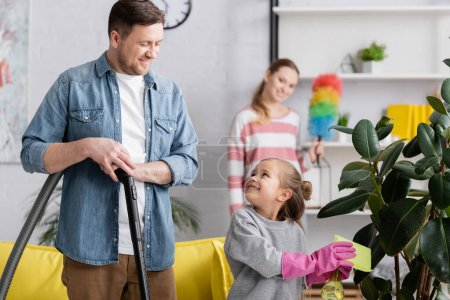 Girl cleaning plant and looking at father with vacuum cleaner at home