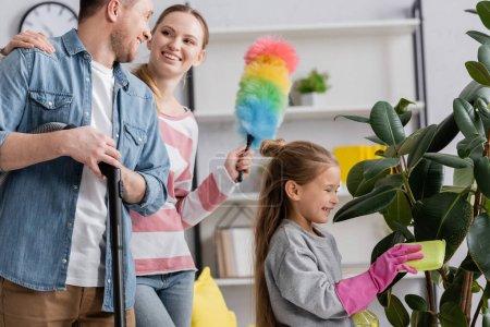 Souriant enfant usine de nettoyage près des parents avec aspirateur et brosse à poussière étreignant
