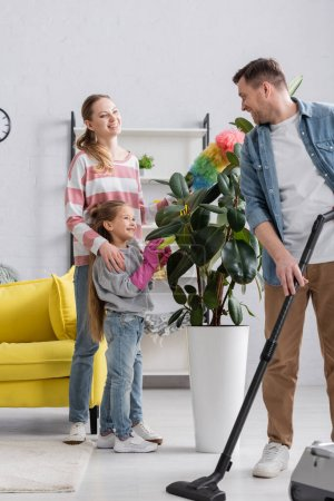Smiling man with vacuum cleaner looking at family near plant at home