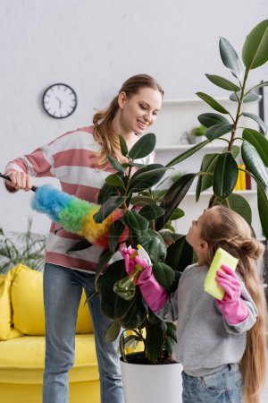 Positive mother with dust brush looking at daughter near plant at home