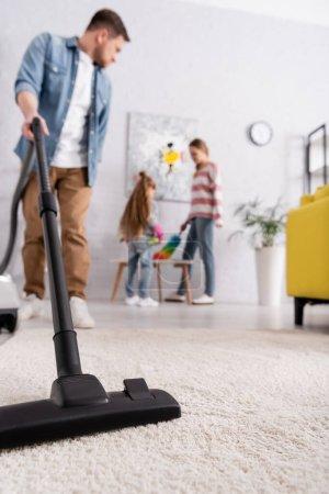 Photo pour Aspirateur en main de l'homme pendant les travaux ménagers près de la famille - image libre de droit