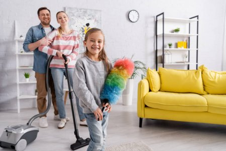 Happy kid holding dust brush near mother with vacuum cleaner and father at home