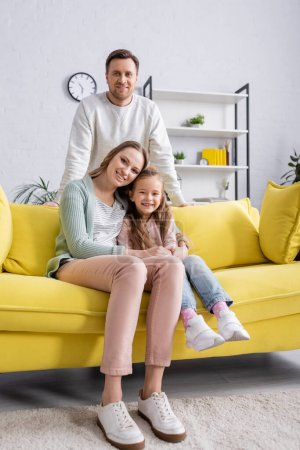 Photo for Woman hugging kid on yellow couch near smiling husband - Royalty Free Image