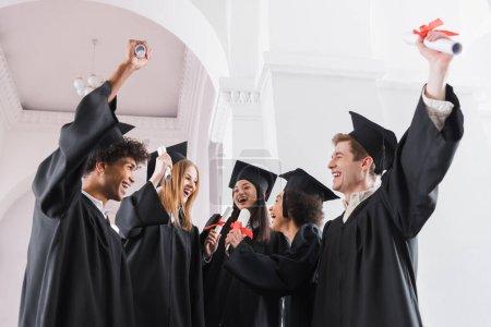 Cheerful multiethnic graduates with diplomas in university